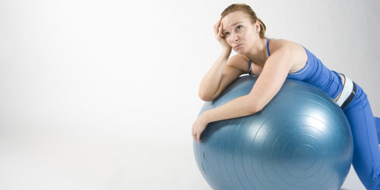 Frustrated woman on exercise ball